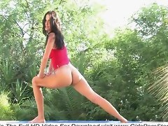 A super sexy brunette is naked outdoor aerobics
