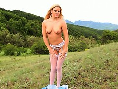Blonde beauty teasing outdoor in forest
