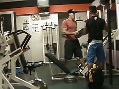 Muscled studs having sex in a gym