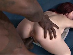 redhead bites her lower lip as she savors the pleasure of hardcore interracial sex